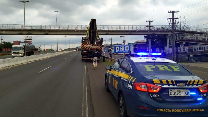 PRF flagra carga com excesso de altura colidindo em passarela na BR-480 em Chapecó