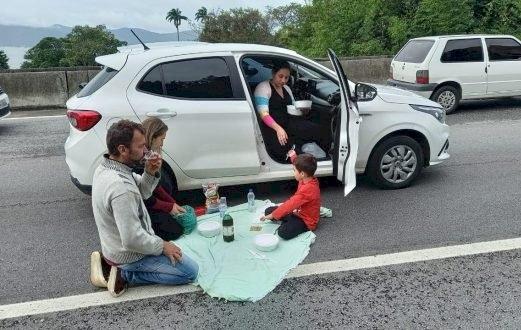 Família faz piquenique fora do carro durante congestionamento na BR-101